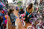 Kacey K.C., with Nevada Division of Forestry, shows with Scarlett and Isabella, both 5, the 15th annual Holiday with a Hero program at Walmart in Carson City, on Wednesday, Dec. 19, 2018. The program, which pairs local heroes with more than 200 K-8th graders, provides a $100 Christmas shopping spree at Walmart.  <br /> Photo by Cathleen Allison/Nevada Momentum