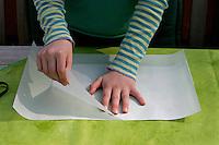 Kinder basteln ein Fensterbild mit Blüten, Mädchen passt zweites Pergamentpapier in der richtigen Größe an