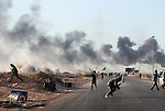 Opposition rebels flee a heavy barrage of artillery and small arms fire near an oil refinery in Ras Lanuf, Libya, March, 11, 2011. Loyalist forces of Col. Muammar Qaddafi pushed rebels back from the strategic oil town with air strikes, artillery and small arms fire.