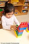 Education preschool 3-4 year olds girl building with Duplo plastic bricks vertical