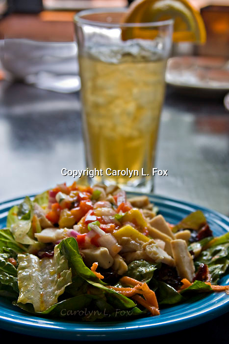 An iced tea is served with a salad.
