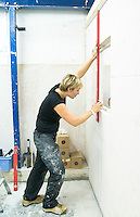 Student doing a course in tiling marking a vertical line.  Able Skills in Dartford, Kent, runs courses in construction industry skills like, bricklaying, carpentry and tiling.