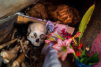 """A dried-up scull and bones are seen placed in a wooden crate inside a niche at the cemetery in Pomuch, Mexico, 26 October 2019. Every year on the Day of the Dead, people of Pomuch, a small Mayan community in the south of Mexico, visit the cemetery to take part in a pre-Hispanic tradition of cleaning of bones of their departed relatives (""""Limpia de huesos""""). People who die in Pomuch are firstly buried for three years in an above-ground tomb then the dried-up bodies are taken out, bones are separated, wrapped in a decorated cloth, put into a wooden crate, and placed on display among flowers for veneration."""