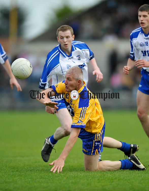 Waterford's Thomas O Gorman keeps the pressure on a grounded David Russell of Clare during their senior championship game in Cusack Park. Photograph by John Kelly.