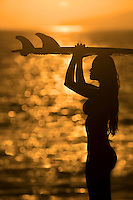 Silhouette of woman surfer at sunset on Maui's west side.