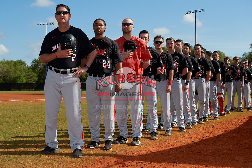 Ball State Cardinals, lead by coaches Rich Maloney (2), Blake Beemer (24), and Dustin Glant, line up for the national anthem before a game against the Saint Joseph's Hawks on March 9, 2019 at North Charlotte Regional Park in Port Charlotte, Florida.  Ball State defeated Saint Joseph's 7-5.  (Mike Janes/Four Seam Images)