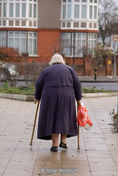 An overweight elderly woman using walking sticks in south London.