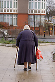 An overweight elderly woman using walking sticks in south London.