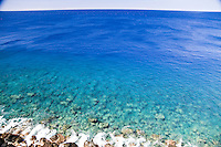Clear blue water and small waves breaking on the rocks at South Point on the Big Island of Hawaii