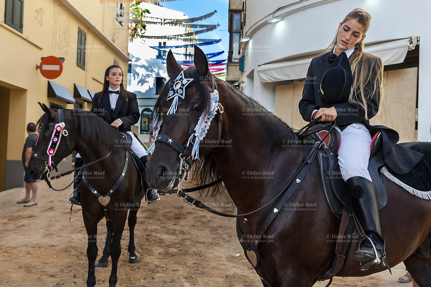 "Spain. Balearic Islands. Minorca (Menorca). Mahon. Two horsewomen at  ""Festes de la Mare de Déu de Gràcia"" during the traditional summer festival. The Menorquín is a breed of horse indigenous to the island and is closely associated with the doma menorquina style of riding. The riders wear black and white and most of their horses (adorned with ribbons and multi-coloured rosettes) are of the highly-considered Menorcan breed. The riders and their horses parade through the streets, and these magnificent and remarkably calm horses rear up on their hind-legs to the delight of the crowd. The most valued quality of Menorquín horse is its suitability for the traditional festivals of Menorca. Horses and riders are at the centre of local fiesta celebrations, in a tradition that may go back to the 14th century and incorporate elements of Christian, pagan and Moorish ritual. Some 150 riders participate in the festival in Mahón. Touching the horses is believed to bring good luck. Maó (in Catalan) and Mahón (in Spanish), written in English as Mahon, is a municipality, the capital city of the island of Menorca, and seat of the Island Council of Menorca. The city is located on the eastern coast of the island, which is part of the autonomous community of the Balearic. In Spain, an autonomous community is a first-level political and administrative division, created in accordance with the Spanish constitution of 1978, with the aim of guaranteeing limited autonomy of the nationalities and regions that make up Spain. 8.09.2019 © 2019 Didier Ruef"