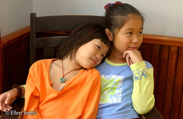 MR / Schenectady, NY. Older sister (9, Taiwanese-American) holds younger sister (6) as they sit together..MR: Yan3 Yan2.©Ellen B. Senisi