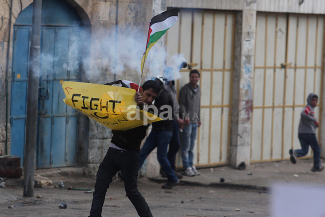 A Palestinian protester holds a placard during a protest against the closure of Shuhada street to Palestinians, in the West Bank city of Hebron February 24, 2012. Some 200 protesters, including foreign and Israeli activists, gathered on Friday marking the 18th anniversary of the closure of the street, which was closed by the Israeli army in 1994 following the Hebron mosque massacre by Baruch Goldstein, an Israeli settler, who went on a rampage inside Al Ibrahimi Mosque, killing 29 Palestinian worshippers. Photo by Issam Rimawi