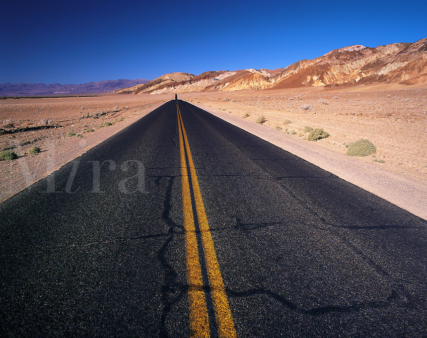 Long, straight, empty tarmac road in Death Valley, with low red-colored hills to the right, California, US