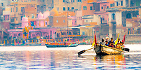 Rowing boat with people on Yamuna River with blurred, colorful boats and buildings in the background, during Holi, in Mathura Uttar Pradesh India