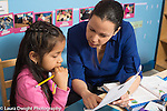 Afterschool homework help program for Headstart graduates Grades K-3 female teacher working with students
