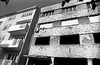 Mostar, un edificio in rovina danneggiato durante la guerra, con fori di proiettile nel muro, a fianco di un palazzo nuovo --- Mostar, the ruin of a building damaged during the war, with bullet holes in the wall and next to a new building
