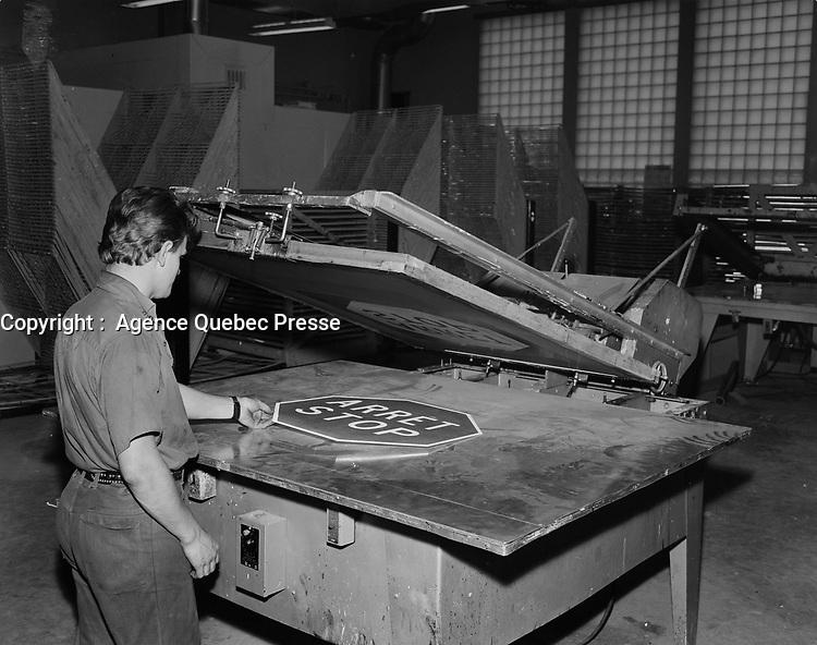 Travailleur manipulant une pressant servant a fabriquer les panneaux STOP - ARRET<br /> , en 1969<br /> <br /> <br /> PHOTO : Agence Quebec Presse