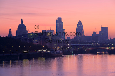 """United Kingdom, England, London: Sunrise over the City of London and River Thames from Waterloo Bridge, showing silhouettes of Saint Paul`s Cathedral and the `Gherkin` (also known as Swiss Re Building)   England, London: Sonnenaufgang ueber London, Blick von Waterloo Bridge auf Skyline mit St. Pauls Kathedrale und """"Gherkin"""" auch bekannt als Swiss Re Building"""