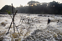 A fisherman checks fishing traps placed in rapids on the Lindi River, a tributary of the Congo River.
