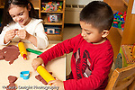Education preschool 3-4 year olds art activity boy and girl sitting side by side playing with play dough rolling pin and cutters playing separately vertical