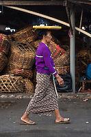 Bali, Indonesia.  Woman Carrying Tray on Head, Incense Burning.  Jimbaran Fish Market.