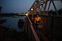 A girl rides her bike across the Da Vien bridge in Hue, Vietnam on 25 February 2010.