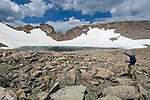 man, (MR), Rowe Glacier, lake, high elevation, alpine, landscape, cumulus, clouds, rocky, snow, summer, August, afternoon, Rocky Mountain National Park, Colorado, USA