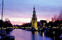 canal, Amsterdam, Holland, The Netherlands, Europe, Scenic view of a canal (grachten) and clock tower at sunset in downtown Amsterdam.