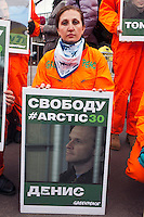 """Moscow, Russia, 05/10/2013.<br /> A Greenpeace activist holds a portrait of Russian photojournalist Denis Sinyakov behind bars in Murmansk court at a demonstration in support of the crew members of the ship """"Arctic Sunrise"""" . The entire crew and accompanying journalists including Sinyakov have been charged with piracy after being seized at gunpoint by Russian coastguards while protesting at a Gazprom off-shore drilling platform In the Arctic."""