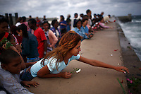 Government employees throw flowers into the ocean in honor of the anniversary of the death of Cuban revolutionary Camilo Cienfuegos along the Malecon in Havana, Cuba on 28 October 2008.