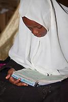 Zanzibar, Tanzania.  Young Girl Reading the Koran in a Madrassa (Koranic School).