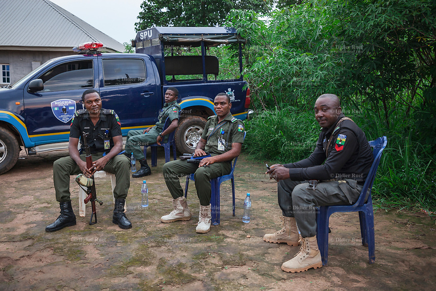 """Nigeria. Enugu State. Owo. Outside Saint Mary's Catholic Parish. A group of four policemen with their Kalashnikovs look after security while seated outside on plastic chairs, A Police off road 4x4 vehicle. Toyota Landcruiser with a sticker on the door: Special Protection Unit, Base 21. A Kalashnikov rifle is an automatic rifle, widely known as Kalashnikovs, AK47s, or as a """"Kalash». 9.07.19 © 2019 Didier Ruef"""