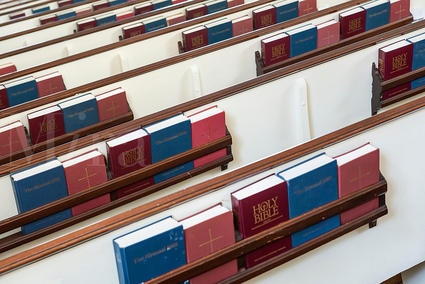 Church pews with prayerbooks and hymnals.