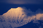 The sun spot lights a snow capped  peak in the Mission Mountains