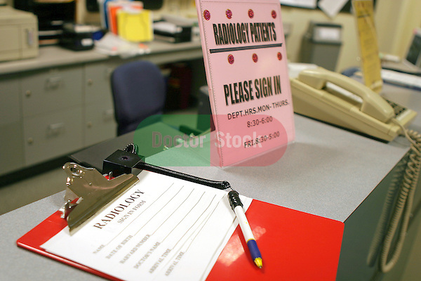 sign-in clipboard and signage on counter of waiting room of radiology lab