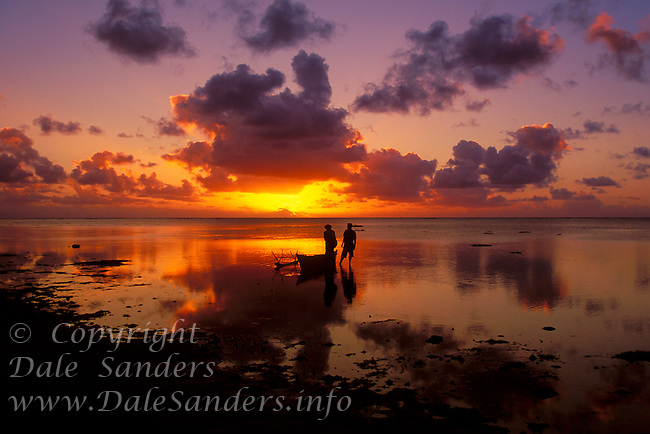 Fisherman and traditional outrigger canoe at sunset, Aitutaki Lagoon,  Cook Islands in the South Pacific.