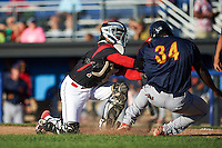 Batavia Muckdogs catcher Pablo Garcia (7) tags Bladimil Franco (34) sliding home during a game against the State College Spikes on June 23, 2016 at Dwyer Stadium in Batavia, New York.  State College defeated Batavia 8-4.  (Mike Janes/Four Seam Images)