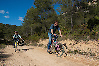Father and son having fun riding their mountain bikes together on a dirt road, Vitrolles, Provence, France.