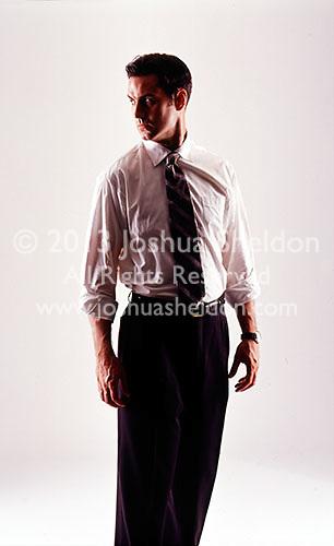 Dramatically lit man wearing business attire on white seamless<br />