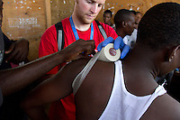 A mass casualty incident drill simulating a helicopter crash, is held in Jean Marie Vincent 2, a tent city in Port au Prince, Haiti for EMT students through EMPACT Northwest.  The students first reviewed their lessons at Boujet Park where they have translated Haitian Creole for English speaking medical personal for almost two years since the earthquake in 2010.  Volunteer instructors from EMPACT NW applied moulage - make up to look like mock injuries- to residents who volunteered for the training drill. Also present were the United Nations Police who have been stationed there for two weeks. The camp is on the site of Haiti's first Airport, Bowen Field.  Several old derelict airplanes and helicopters litter the area and are being used by people for shelter.  (photo copyright Karen Ducey)