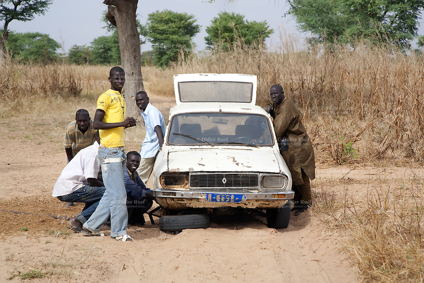 Senegal. Province of Thies. Village Nekhe Niane. On a dirt road, a group of men change a car's flat tyre. 04.12.09  © 2009 Didier Ruef