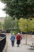Two elderly women walk along a canal towpath in Paddington, London.