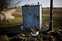 "Jon Fighter digs behind an old outhouse in hopes of reviving it for the campsite before the summer season brings business to the Crow Indian Reservation. ""I'll take any work I can get,"" said Fighter, who was working for the white man who owns the property. ""It's much better than traveling to Billings everyday, and not being sure if I will be able to find work."""