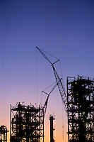 A petrochemical refinery under construction with scaffolding and cranes in the foreground and a distillation tower in the background.