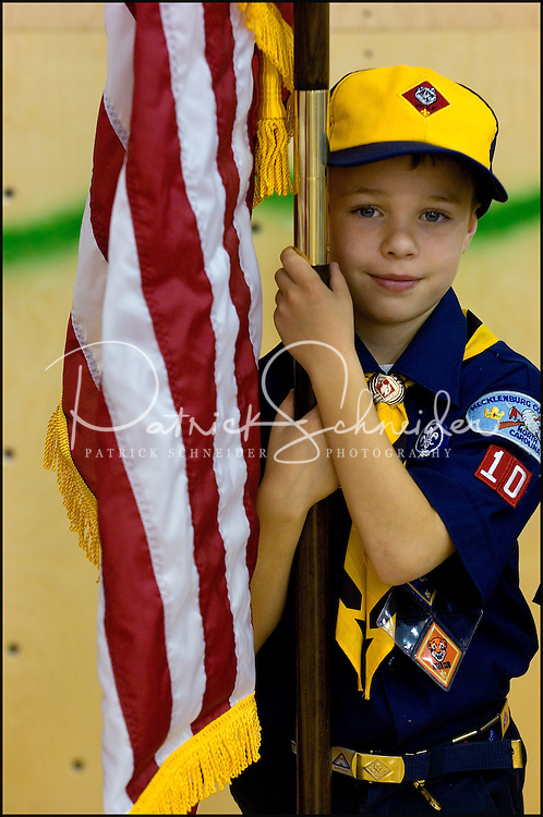 A cub scout holds the American flag during a ceremony.