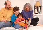 19 month old toddler girl with parents and older brother age 9 reading board book (adopted from Vietnam as an infant)