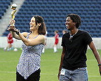 Kate Markgraf holds up the World Cup trophy as Briana Scurry looks on.  The players were at the game as the Red Stars honored the 10th anniversary of the U.S. National Team's 1999 World Cup championship.  The Chicago Red Stars defeated the FC Gold Pride 3-1 at Toyota Park in Bridgeview, IL on July 12, 2009.
