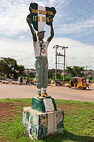 """Nigeria. Enugu State. Enugu. Town center. On a roundabout, a sculpture from a man who is member of the """"National Youth Service Corps"""" with the written words: """"Shun Corruption. It's evil"""". In Igbo language Shun means don't engage or avoid. The National Youth Service Corps (NYSC) is a scheme set up by the Nigerian government to involve Nigerian graduates in nation building and the development of the country. There is no military conscription in Nigeria, but since 1973 graduates of universities and later polytechnics have been required to take part in the National Youth Service Corps program for one year. A few yellow auto rickshaws used by """"Keke"""" drivers for transporting people around town are waiting on the side of the road.. The tricycle better known in Nigeria as the Keke NAPEP is gaining the dominance on Nigerian roads sweeping every street of cities and villages. The auto rickshaw is a common form of urban transport, both as a vehicle for hire and for private use. Enugu is the capital of Enugu State, located in southeastern Nigeria. 2.07.19 © 2019 Didier Ruef"""