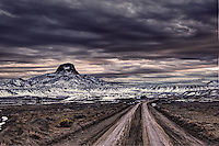 A dirt road in the Cabezon Wilderness Study Area of the Rio Puerco Valley in the San Juan Basin of northwestern New Mexico at twilight in winter.