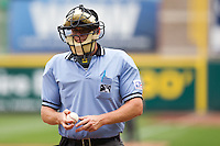 Home Plate Umpire Brandon Misun cleans a ball during a game between the Arkansas Travelers and the Springfield Cardinals on May 10, 2011 at Hammons Field in Springfield, Missouri.  Photo By David Welker/Four Seam Images..